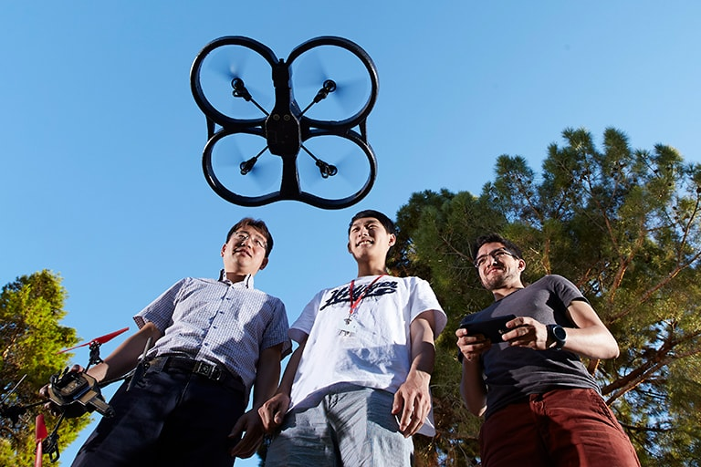 Two students and a professor operating a drone