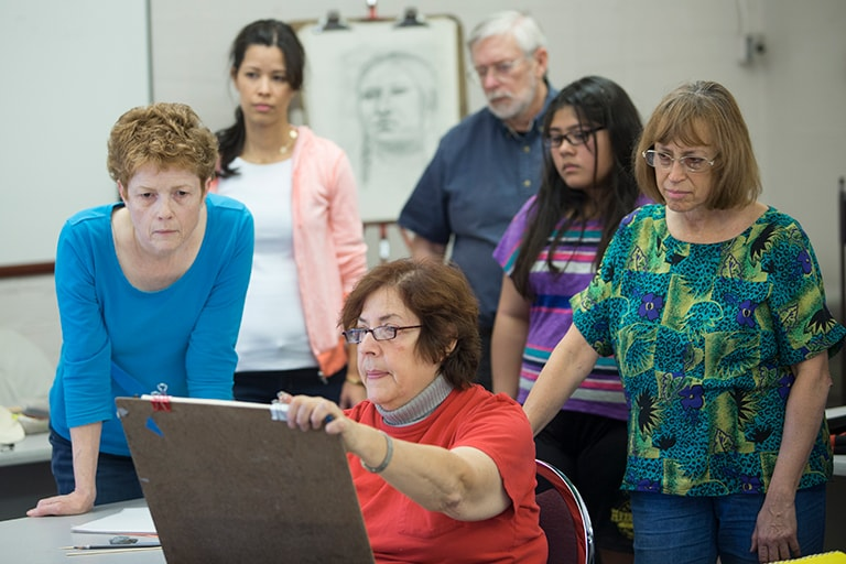 students look over instructor's shoulder as she show's artwork