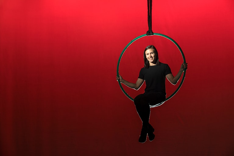 Emily Black sits on hanging hoop with red background