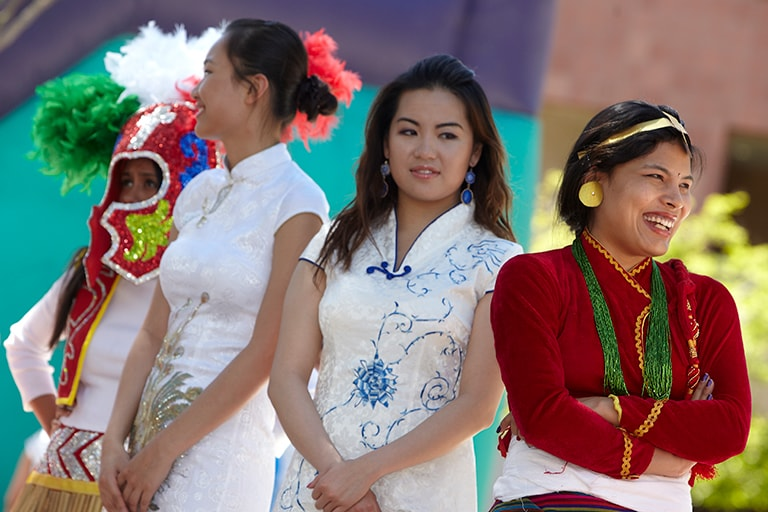 Female performers dressed in various tranditional ethnic clothing