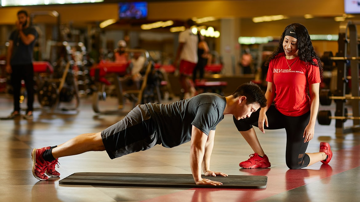 Trainer helps student with push ups