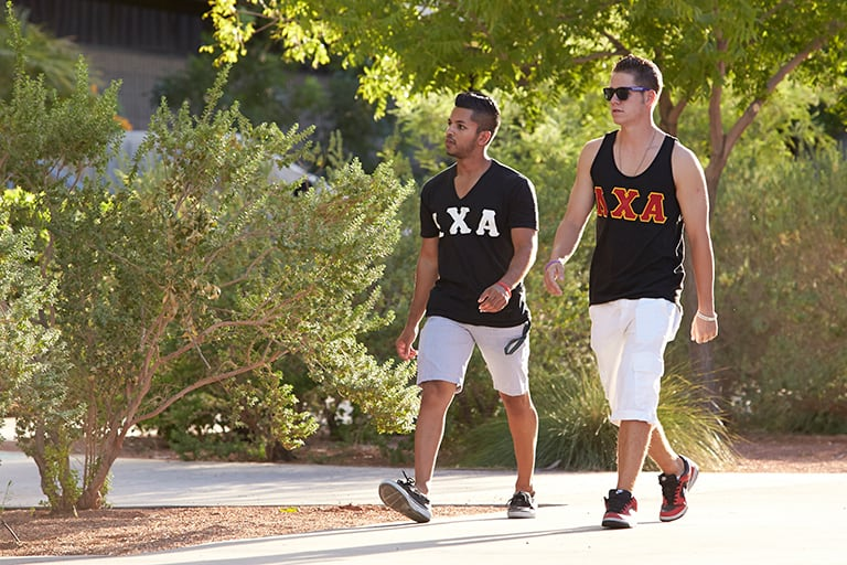 Two fraternity members walking