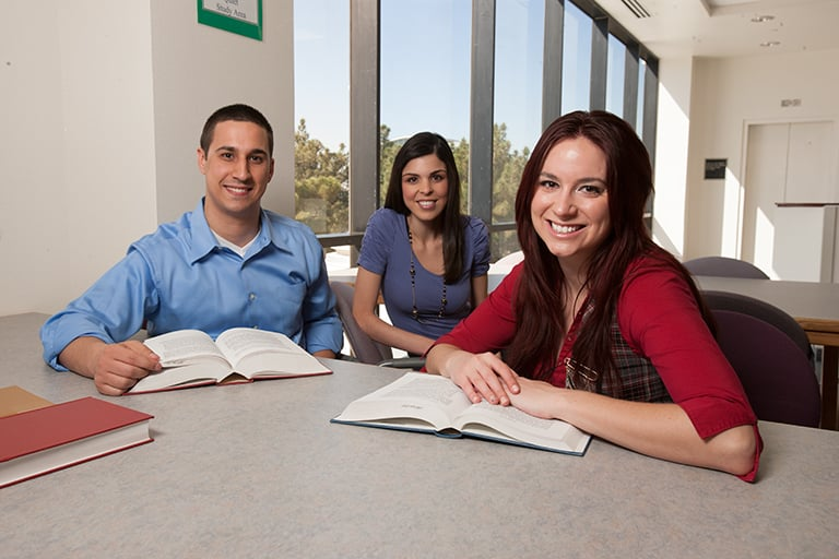 Three smiling students sitting at a table with open books.