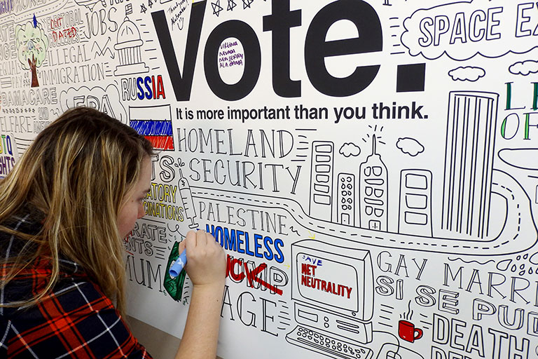 Student using a marker to color an infographic about voting