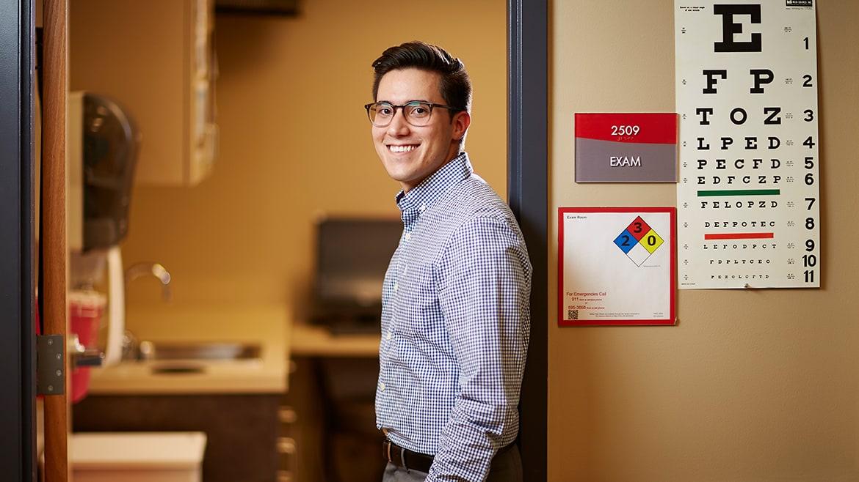 Student doctor standing in doorway of exam room