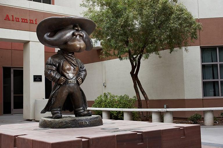 Bronze mascot statue on platform in courtyard