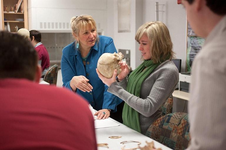 Student examines a skull