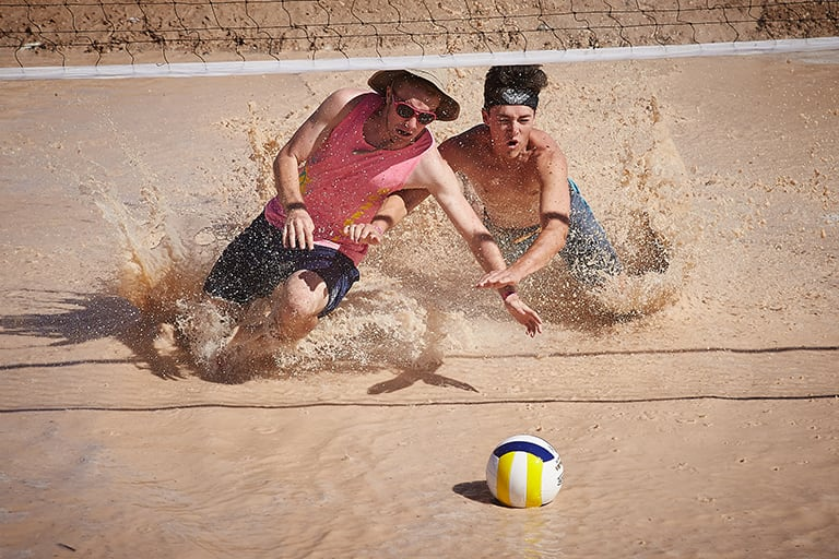 two people race towards volleyball in muddy water