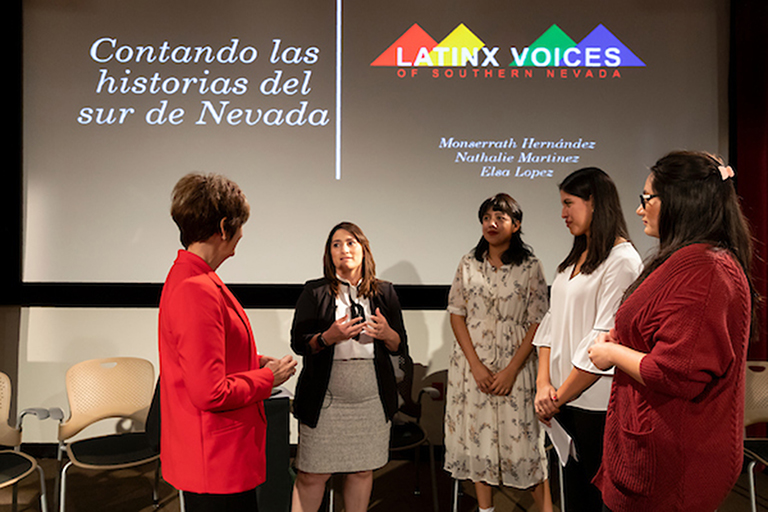 Group of five women standing in front of a screen. The screen has a slide from a presentation about Latin-x voice in southern Nevada.