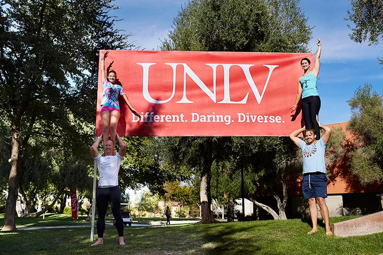 Students on campus in front of a U-N-L-V sign that reads Different. Daring. Diverse.
