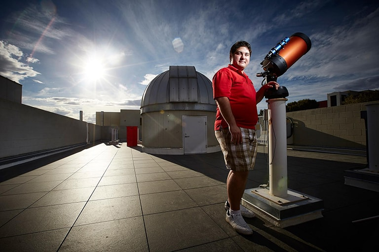 Student stands in front of a telescope