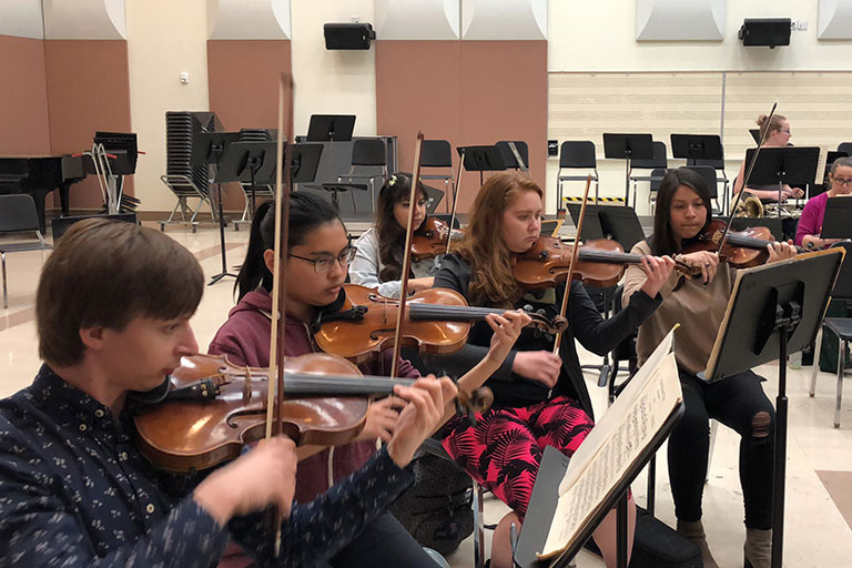 Students playing string instruments