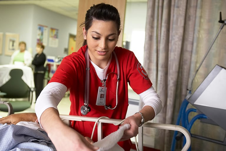 Female nursing students working on a simulation dummy in a hospital bed