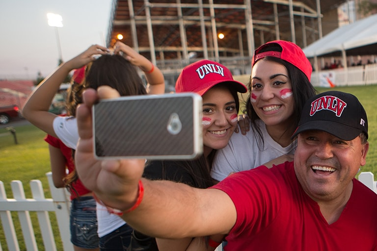 Father takes selfie with two daughters wearing U.N.L.V. caps