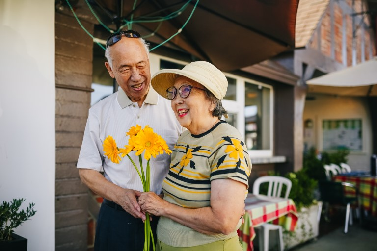Woman holding flowers and man smiling