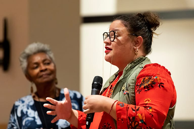 Woman speaking into a microphone, another woman in the background looking at the first
