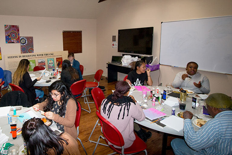 A group of people seated at different tables working on creative projects while eating food and talking to each other.