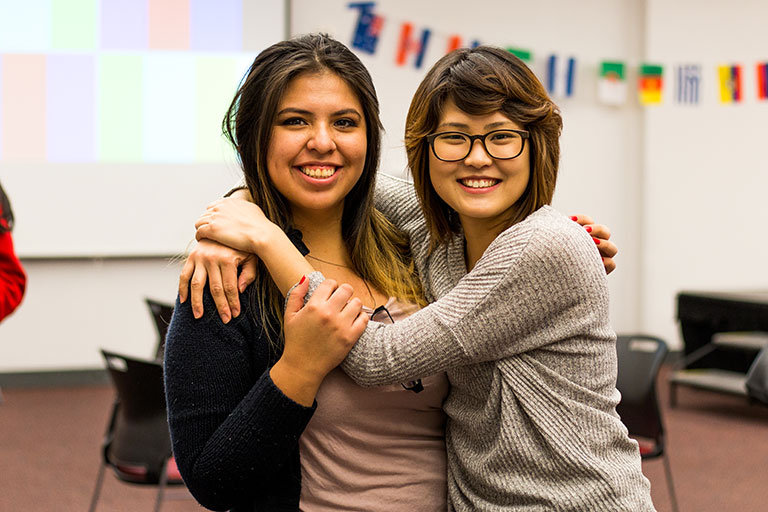 Two female students hugging and smiling inside a classroom.