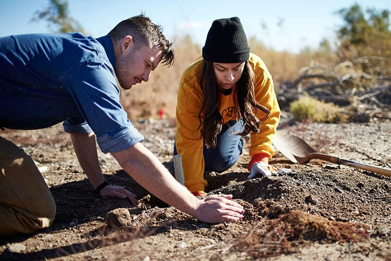 Two students planting seeds