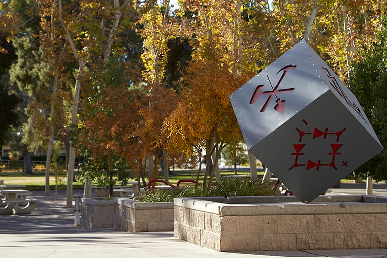 Alumni cube sculpture with red markings on each side
