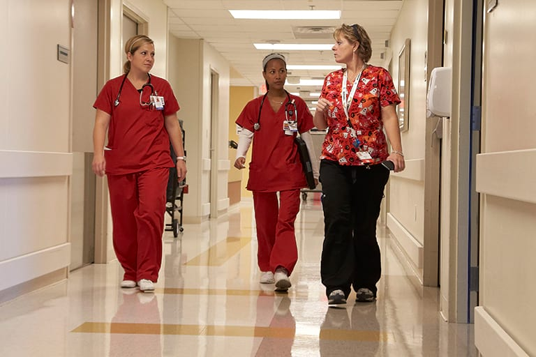 Nurses walking down a hallway.