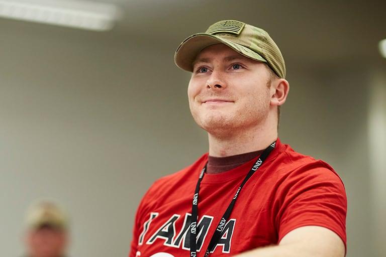 student wearing a veteran cap