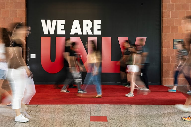 Students walking past wall that says We Are U.N.L.V.