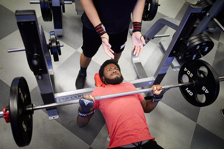 Student lifting weights on bench