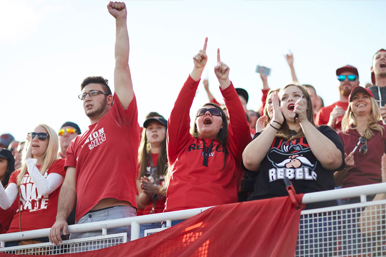 Guests at a UNLV game, cheering.