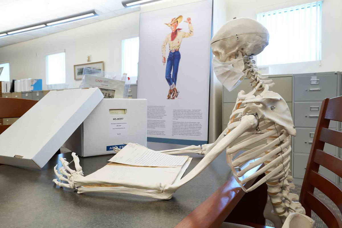 A skeleton sits at a table reading a book