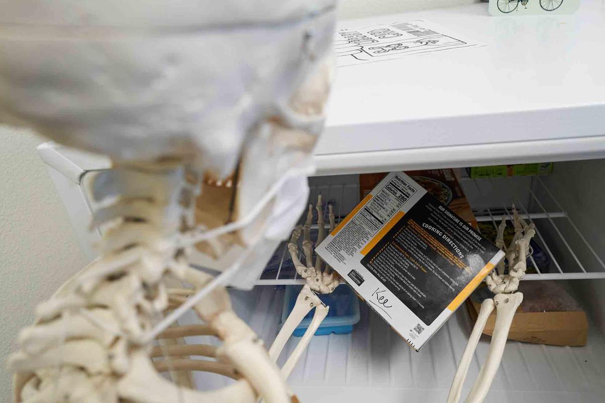 A skeleton takes a box out of a freezer