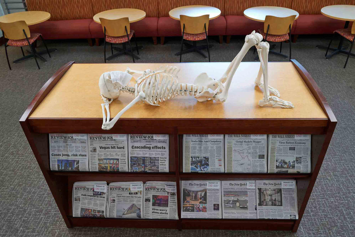 A skeleton lays across a rack of newspapers