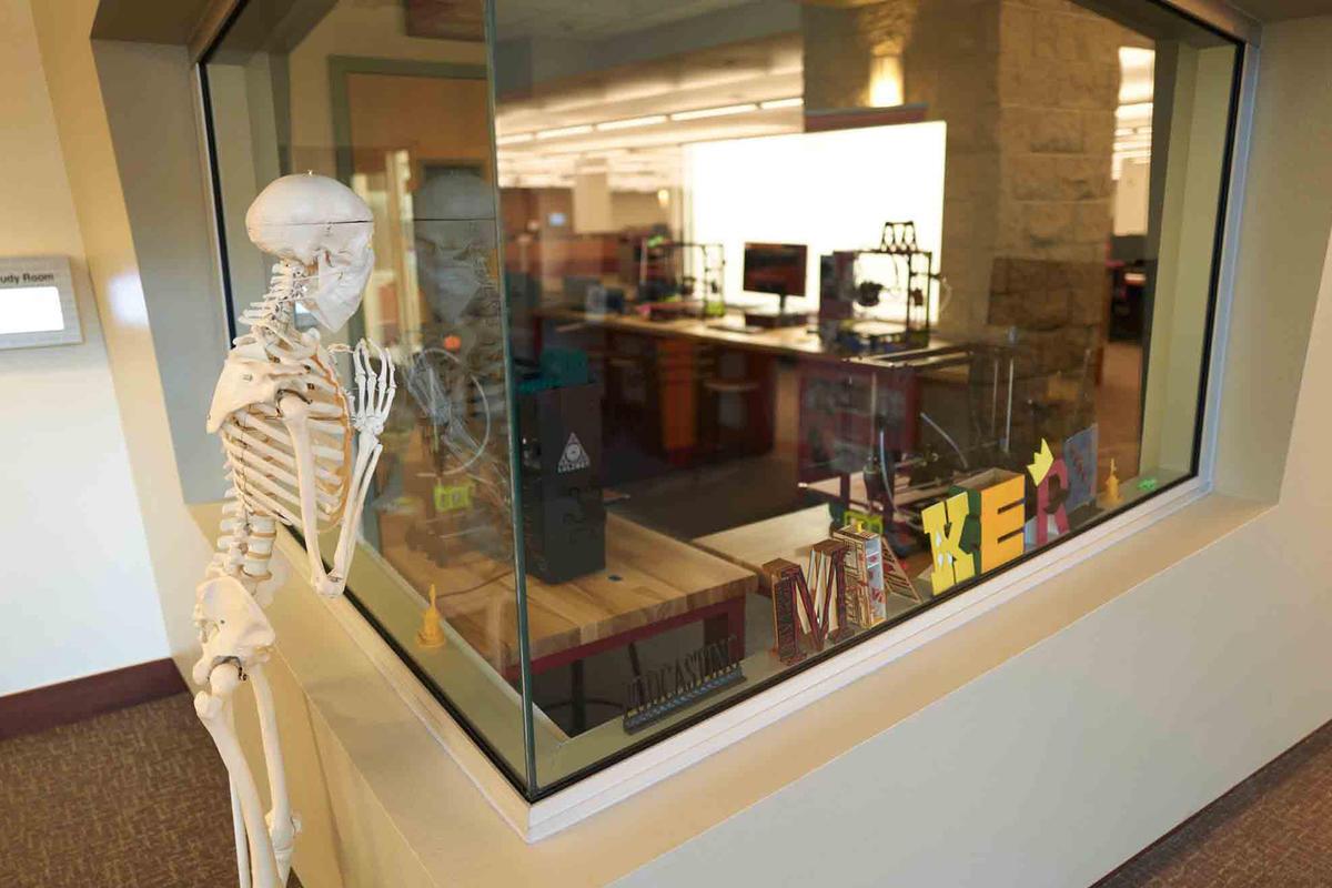 A skeleton peers through a glass wall