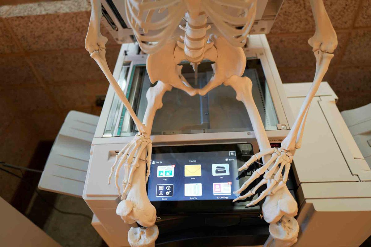 A skeleton sits on a copy machine