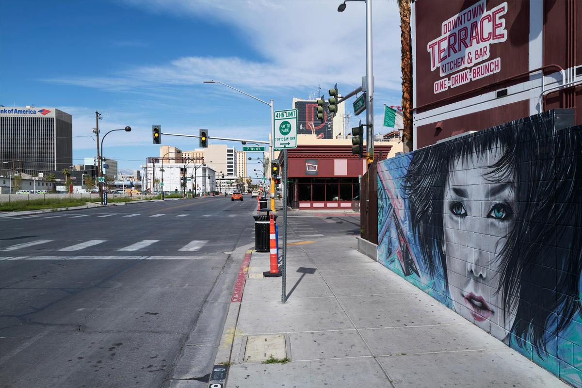 A mural of a woman overlooks an empty street