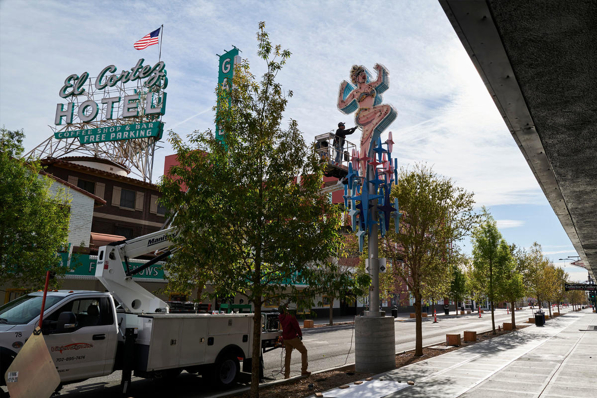Two workers adjust a neon sign across from the El Cortez