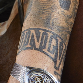 A black-line tattoo shows the arched UNLV logo on a man's wrist.