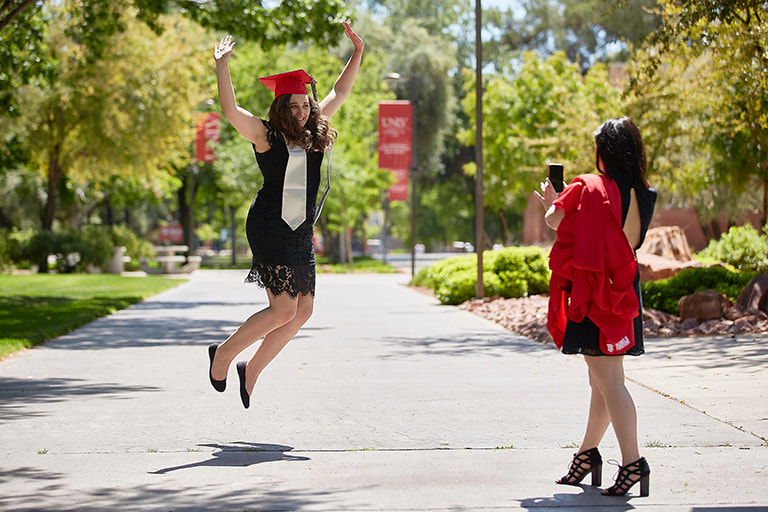 Graduating student jumping in the air for a photo.