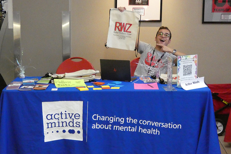 A table for active minds with a representative holding up a Rebel Wellness Zone bag.