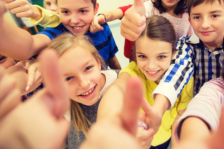 Group of elementary students smiling and giving thumbs up