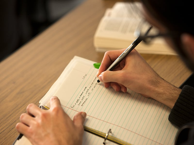 A student writing notes down in a notebook.