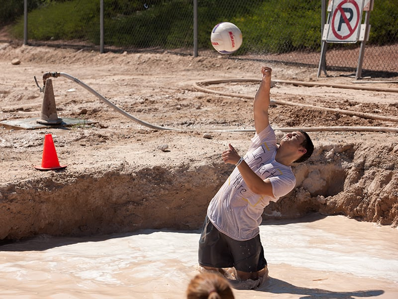 A Student serving the oozeball over the net in a pool of water.