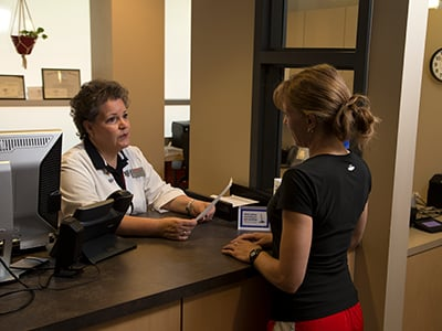 A student receiving service at the front desk of the student health center.