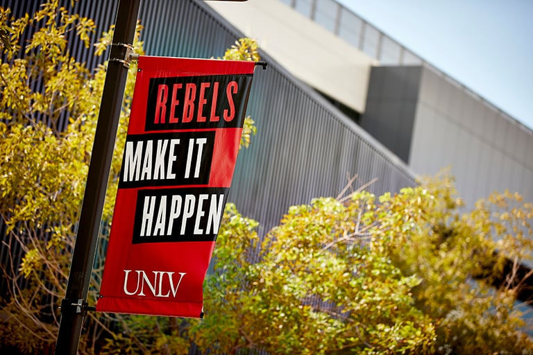 Rebels Make It Happen branded statement on signage with the U-N-L-V brand at its base, on campus.