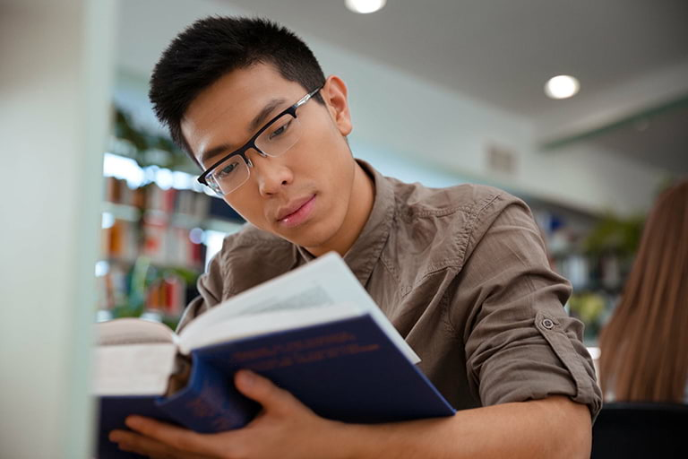 A man reading a book in the library.