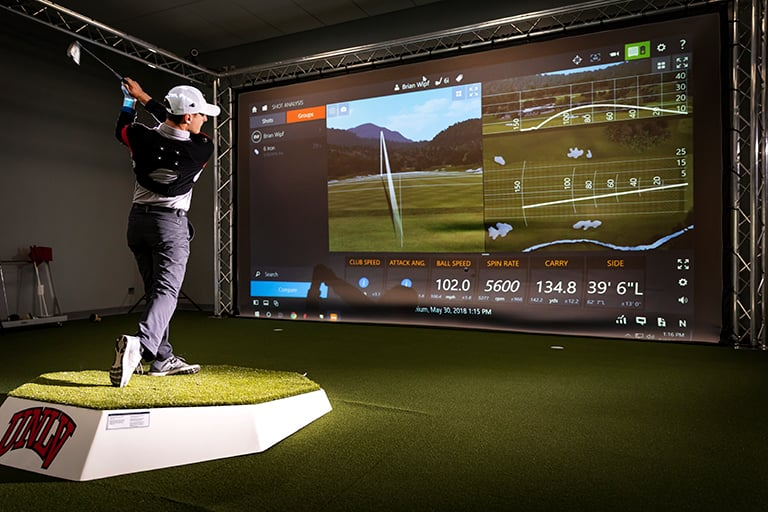 A golfer in a lab swinging and showing stats on a large screen.
