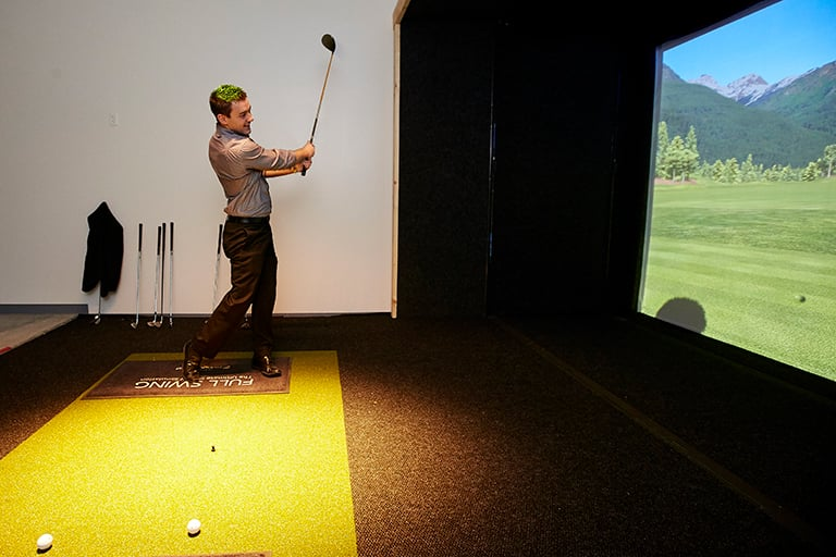 A student playing golf on a simulator screen.