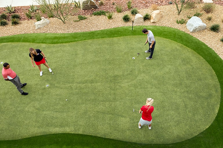 Students using a small putting green to practice putting technique.