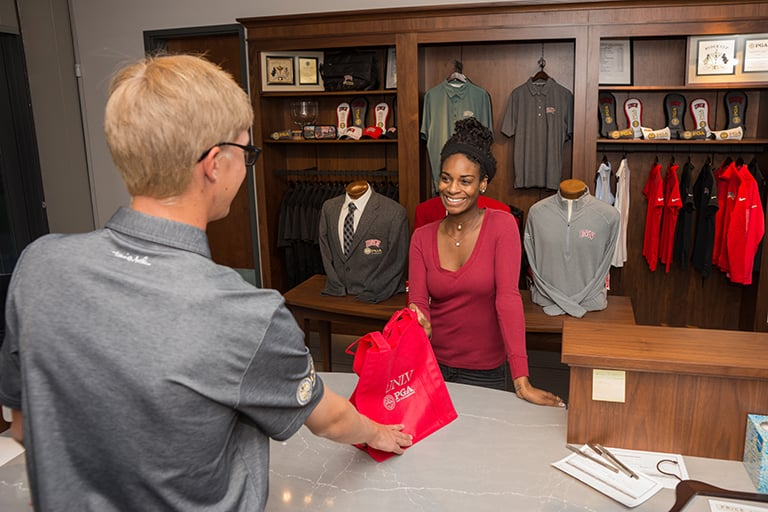 A retail store with golf merchandise being purchased by a customer.