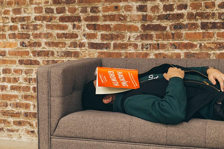 A student asleep on a sofa with a book over their face.
